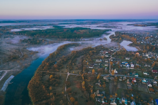Красивый осенний пейзаж с туманом и спальный район на реке. вид с дрона