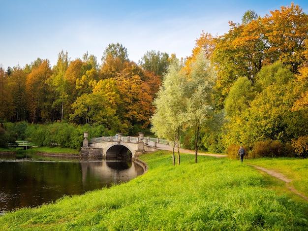 赤い木と湖に架かる古い石の橋のある美しい秋の風景。パブロフスク。ロシア。