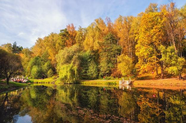 モスクワのツァリツィーノ湖のほとりに赤い木々がある美しい秋の風景 Premium写真