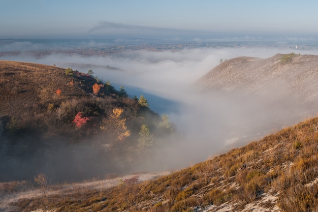 강과 계곡의 안개 낀 숲, 안개 속에서 백악질 언덕 아름다운 가을 풍경