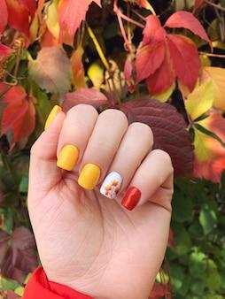 깔끔한 여성 손톱에 아름다운 가을 매니큐어 디자인. 부드러운 사각형 모양. 가을 잎