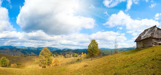Красивая осенняя гора и небольшая деревня на склоне горы (карпаты, украина). два кадра сшивают изображение.