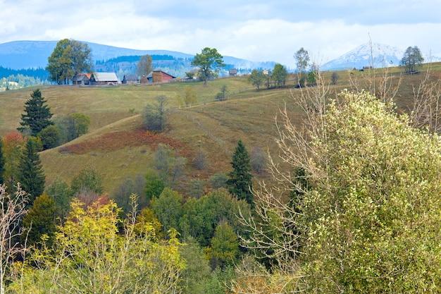 美しい秋の山と山腹の小さな村(カルパティア山脈、ウクライナ)