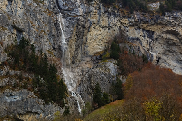 Beautiful autumn time at village of lauterbrunnen in swiss alps, gateway to famous jungfrau. set in a valley featuring rocky cliffs and the roaring