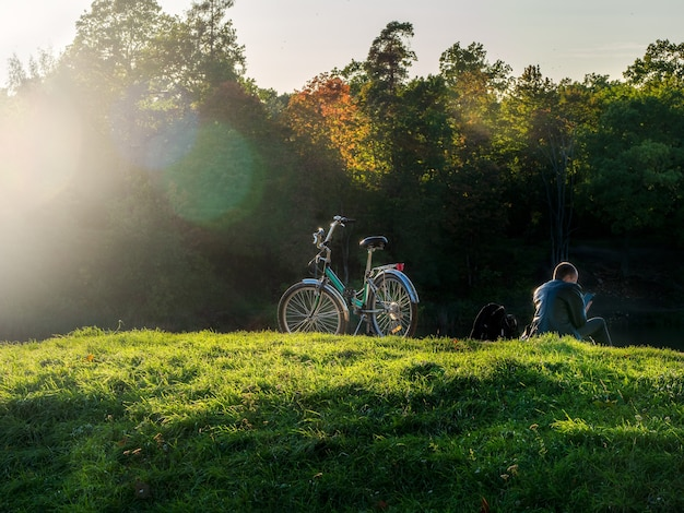 日光を背景に丘の上でサイクリストが休んでいる美しい秋の景色。