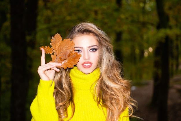 Beautiful autumn woman with autumn leaves on fall nature background autumn outdoor portrait of beaut...