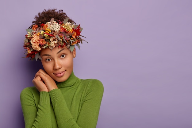 Beautiful autumn young lady looks calmly at camera, leans at both hands, wears wreath made of seasonal plants and leaves, dressed in green poloneck, has relaxed facial expression, poses indoor