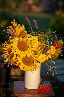 Красивый осенний букет ярко-желтых цветов подсолнечника в белой вазе на деревянном столе в сельской местности. осенний натюрморт с садовыми цветами.