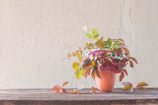 배경 흰색 벽에 나무 테이블에 아름 다운 단풍 구성