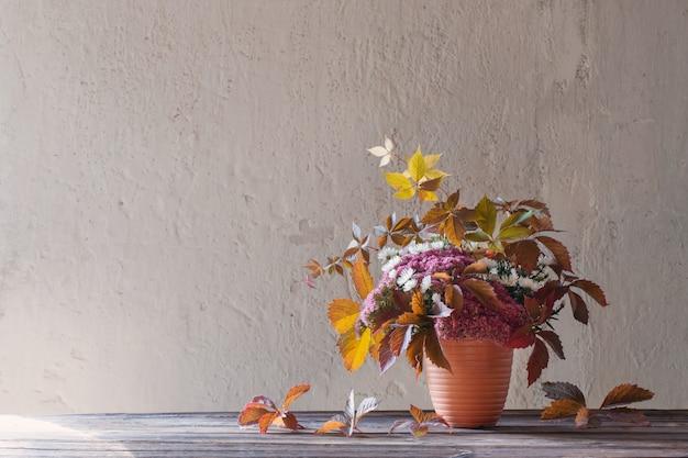 Красивая осенняя композиция на деревянном столе на фоне белой стены