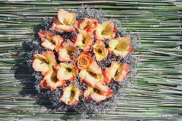 緑の壁に美しい秋のオレンジ色の花の花束。上面図、コピースペース