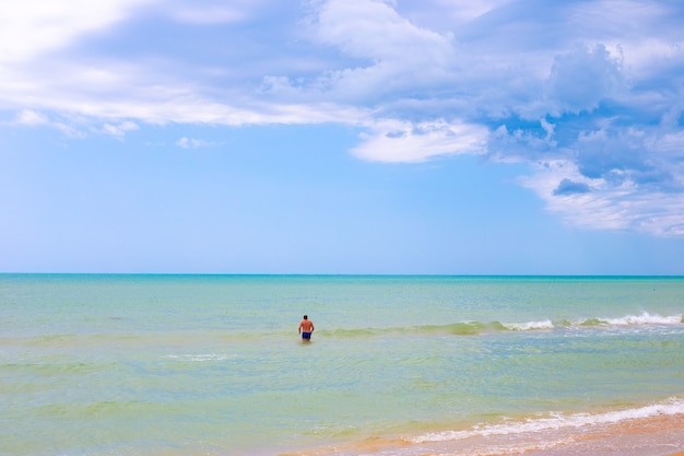 Beautiful azure sea and blue sky on the horizon. a man in the water in the background. idyllic sea landscape.