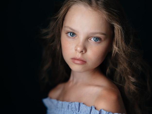 暗い壁に巻き毛のサンドレスで美しい赤ちゃん青い目の女の子