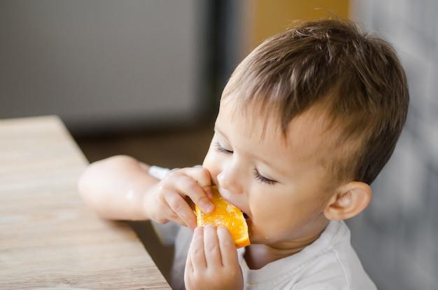 Красивый мальчик на кухне с нетерпением ест апельсин, нарезанный дольками