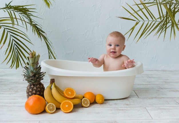 Beautiful baby boy sits in a tub of citrus fruits on a wooden surface with a place for text