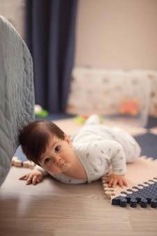 Красивый мальчик с темными волосами в яркой пижаме учится ползать и лежать на животе на полу в детской
