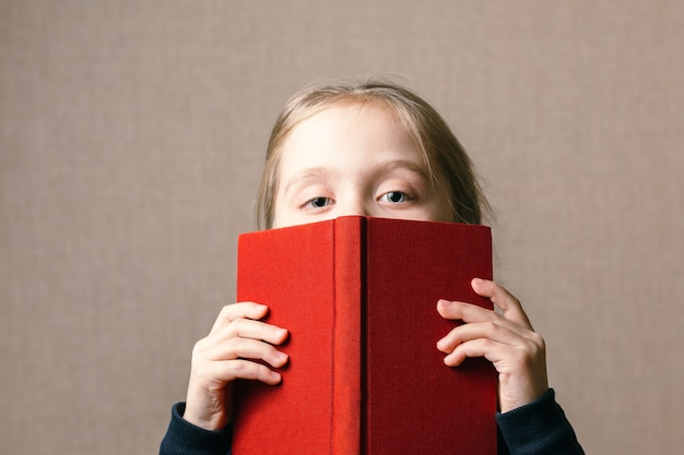 Beautiful baby covering her face with a book