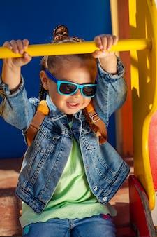 公園でおさげのサングラスの美しい女の赤ちゃん