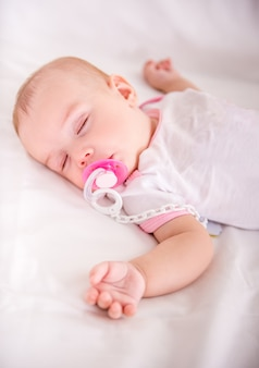 Beautiful baby girl is sleeping in her bed.