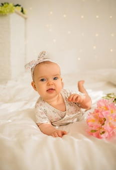 Beautiful baby girl lies in bodysuit next to flowers on the bed