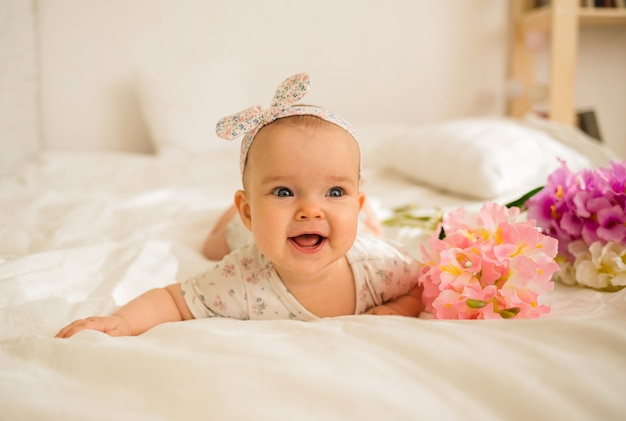 Beautiful baby girl lies and smiles with flowers on bed