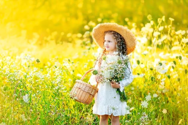 花畑に立っていると夏にバスケットを持って美しい女の赤ちゃん