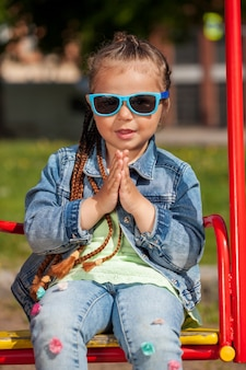 Красивая девочка с косичками и солнцезащитными очками в парке, сидя на качелях