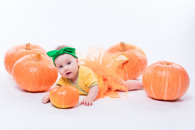 Beautiful baby girl in a yellow body with green bow on her head