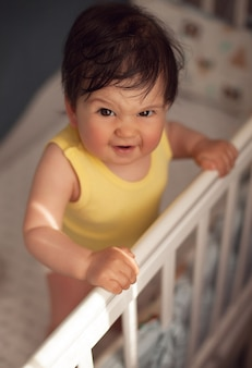 Красивый малыш в желтом теле стоит держаться за кроватку и прячется на солнышке за решетку кровати