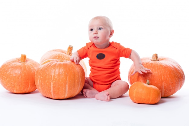 Красивый малыш в оранжевой футболке на белом сидит