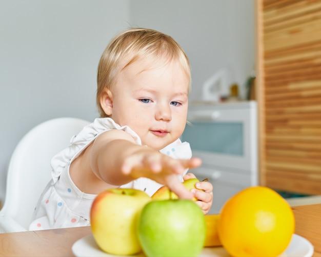 Красивый ребенок смотрит и тянется к фруктам на тарелке.