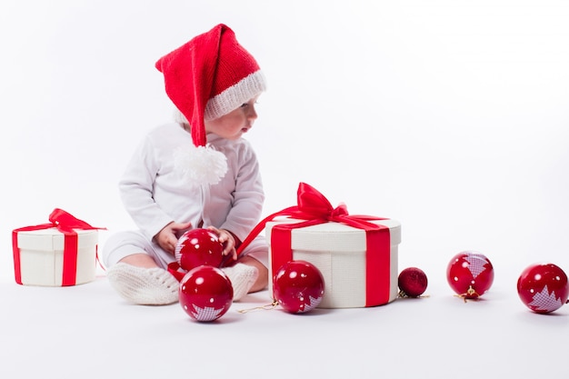 Beautiful baby in the new year's cap and white body sits among
