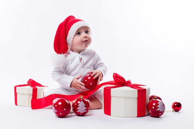 Beautiful baby in the new year's cap and white body sits with christmas gifts or presents