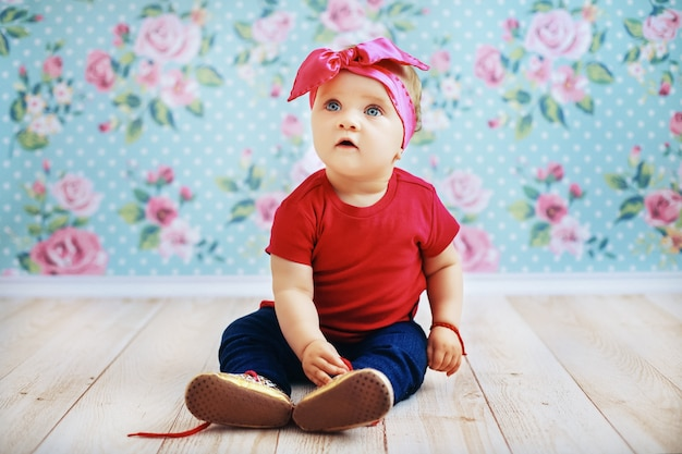 Beautiful baby in a pink jacket and jeans sitting on the floor. parenting.