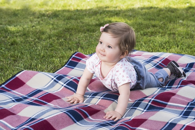 Beautiful baby playing with bunny on blanket