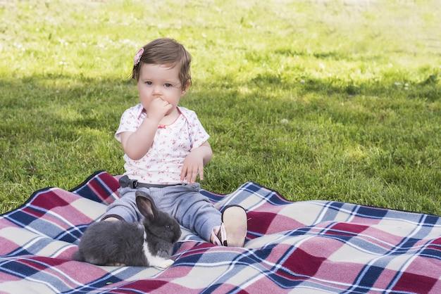 Красивый ребенок играет с кроликом на одеяле