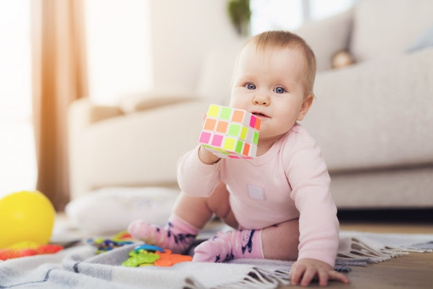 Beautiful baby sits on the floor and plays with bright.