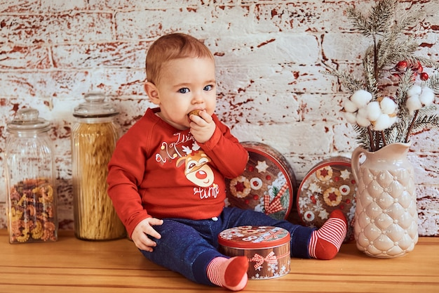 Beautiful baby sits at the table and is eating a nut