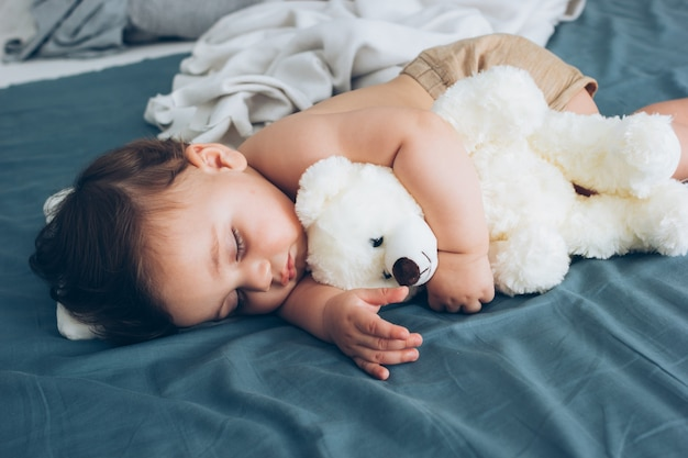 Beautiful baby sleeping with his teddy bear aside, family concept