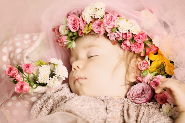 Beautiful baby with flowers and accessories