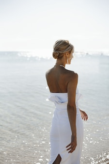 Beautiful back view of a young blonde woman in white dress is walking near the sea on the sunny day