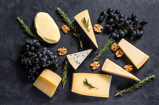 Beautiful background with different types of delicious cheese, walnuts and grapes. top view