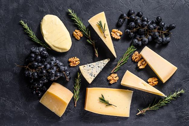 Красивый фон с разными видами вкусный сыр, грецкие орехи и виноград. вид сверху