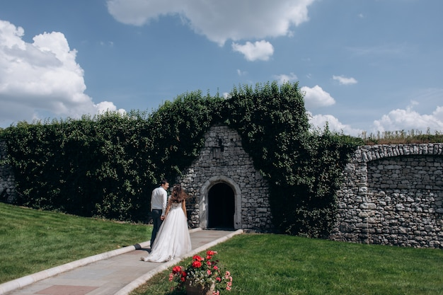 Beautiful backview of a married couple in front of  entrance in the stone wall outdoors