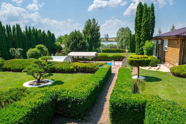 Красивый сад на заднем дворе с красиво подстриженными деревьями, кустами и камнями. ландшафтный дизайн. фото высокого качества