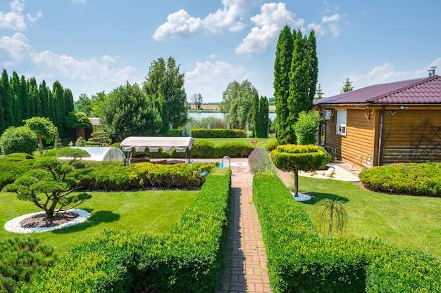 Красивый сад на заднем дворе с красиво подстриженными деревьями, кустами и камнями.