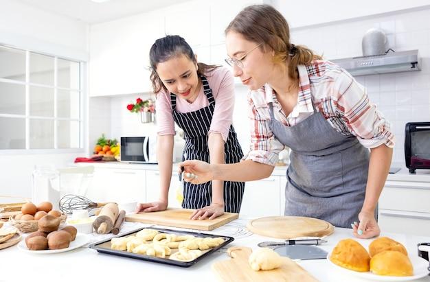 Прекрасный пекарь делает выпечку, симпатичные счастливые две женщины веселятся в классе по выпечке хлеба и руками складывают тесто, чтобы вместе испечь пироги на домашней кухне.