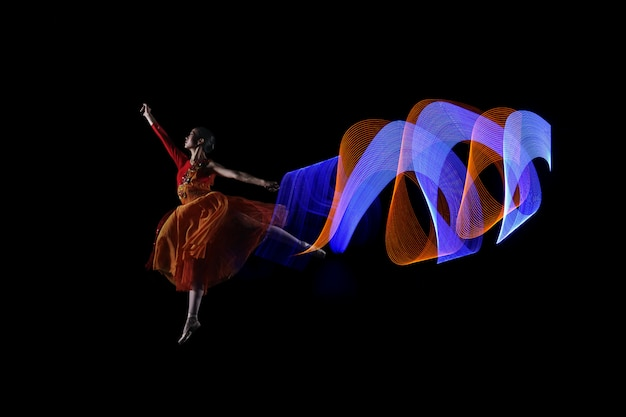 Beautiful ballerina dancer with colorful lights effect