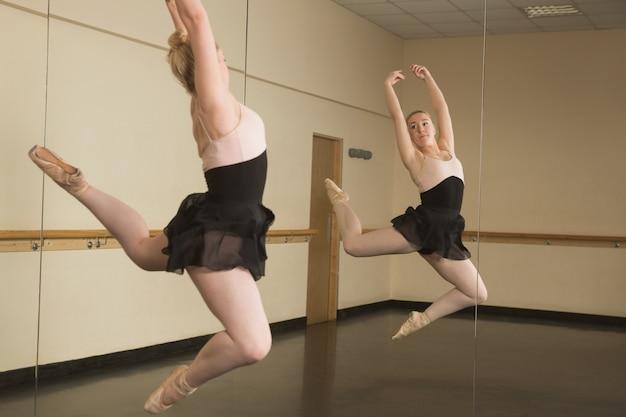 Beautiful ballerina dancing in front of mirror