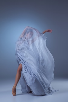 Beautiful ballerina dancing in long blue dress on blue background